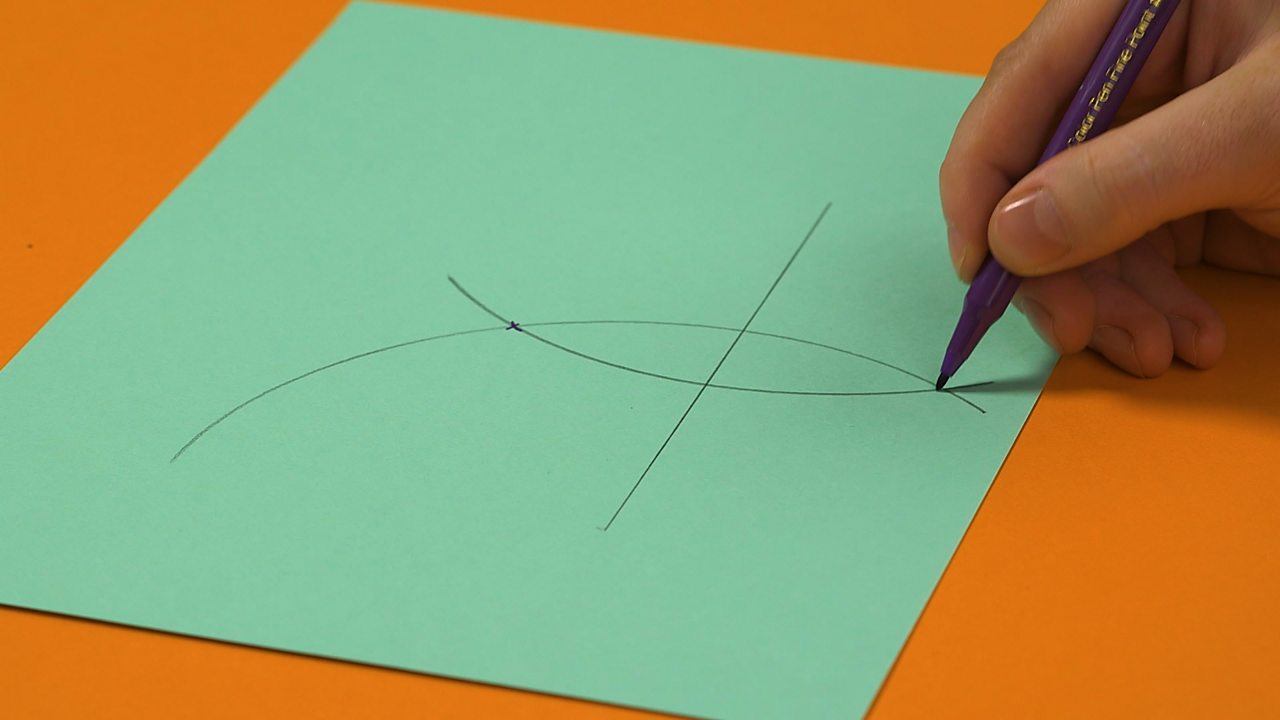 Someone marking the points where the two curved arcs cross each other