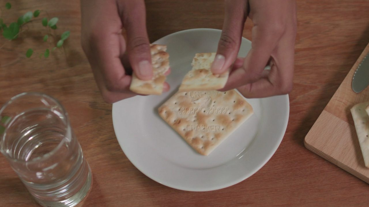 An image of several cream crackers and a glass of water