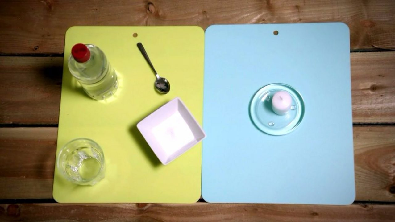 An image showing vinegar, bicarbonate of soda, a small glass, a teaspoon and a candle.