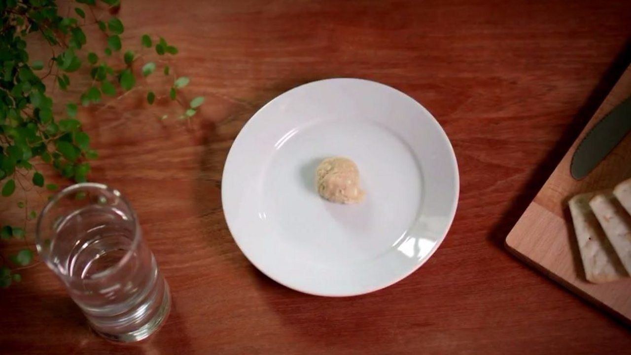 An image of cracker mush on a plate next to a glass of water
