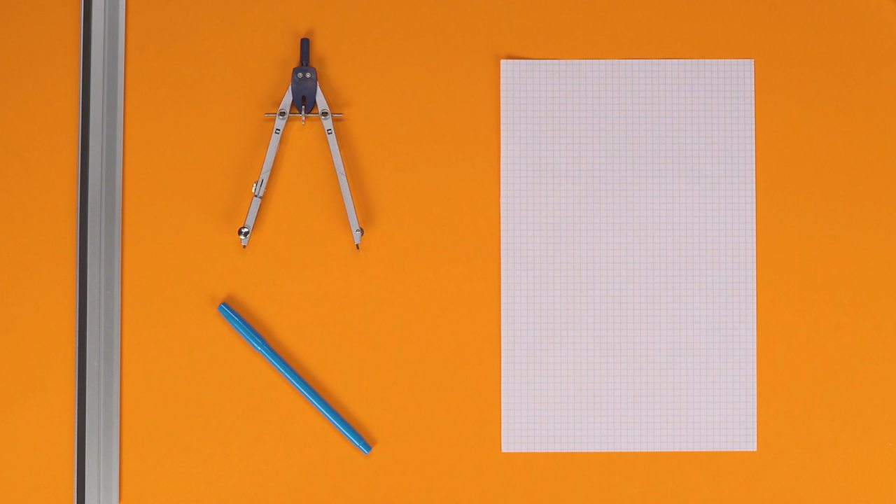 An image showing squared paper, a pen, a ruler and a compass.