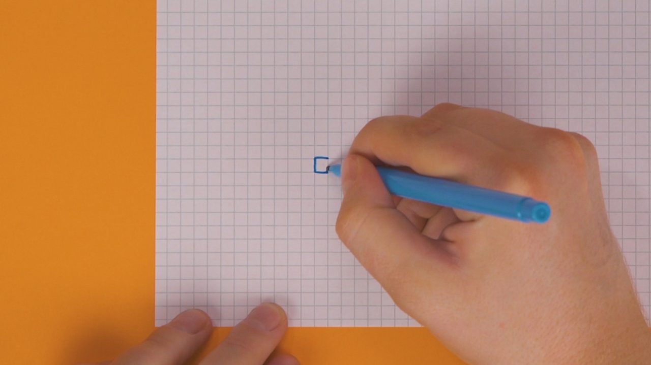 Someone drawing a square onto squared paper