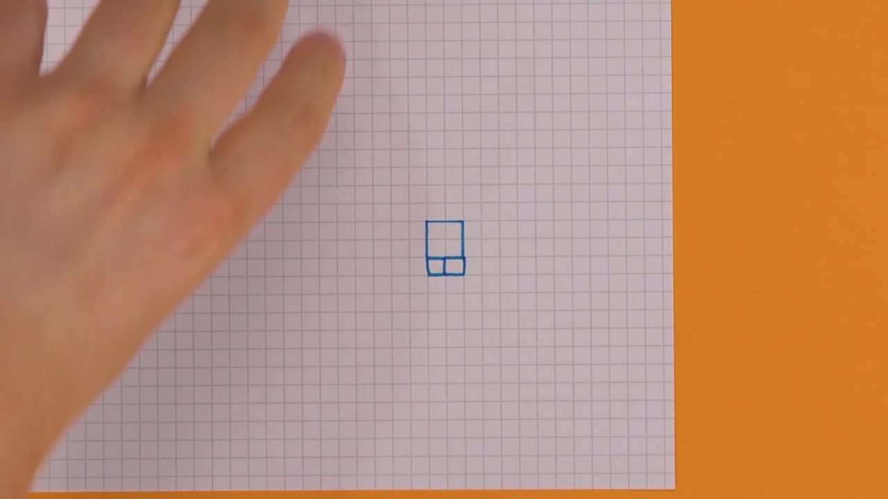 Someone drawing a bigger square on top of two little squares