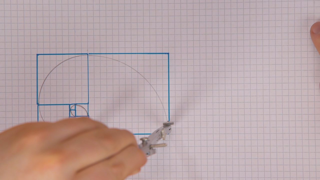 Someone using a compass to draw quarter circles in the larger squares