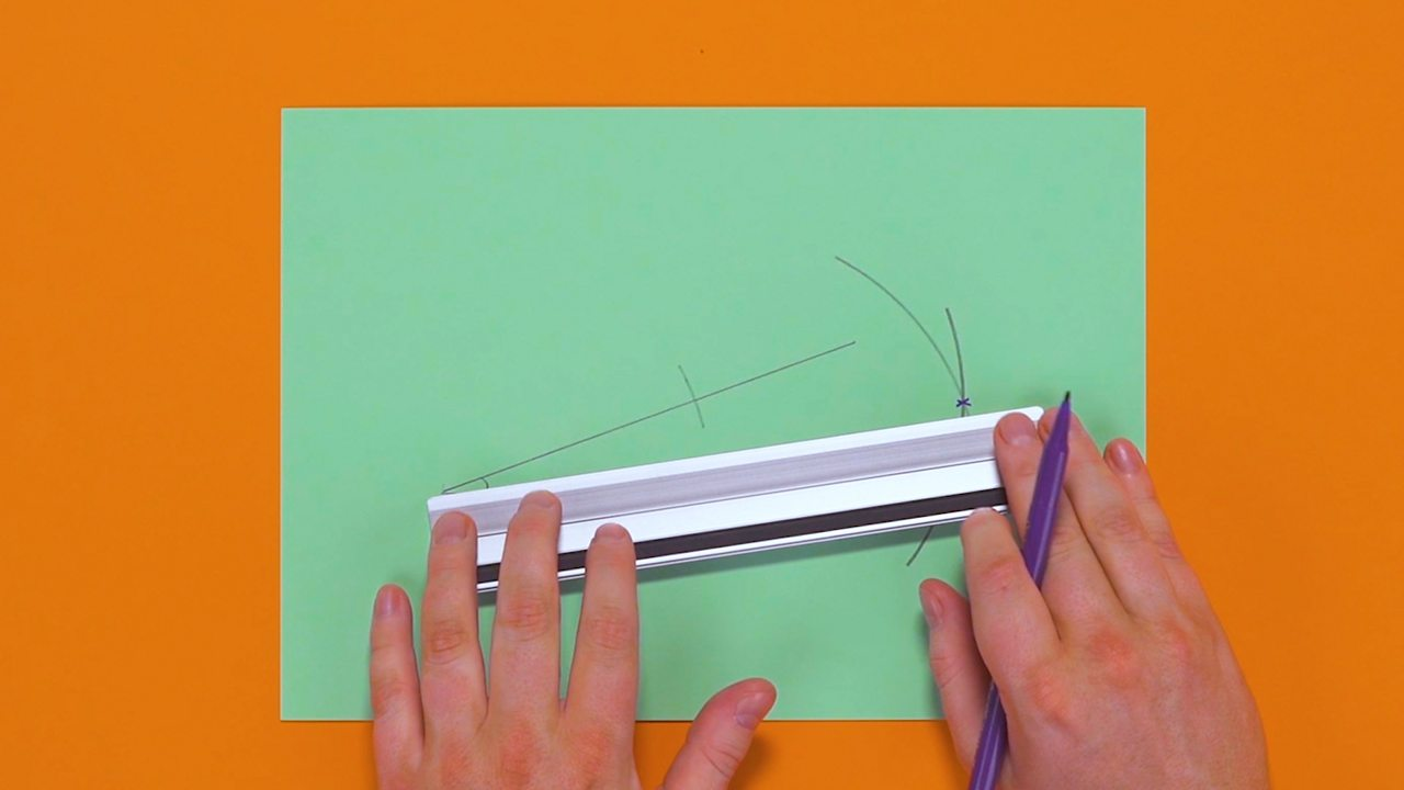 Someone using a ruler to draw a line from the angle to the intersecting curves