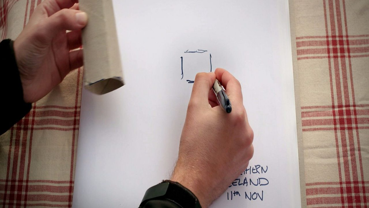 Someone drawing a square trace on the piece of paper from the toilet roll tube