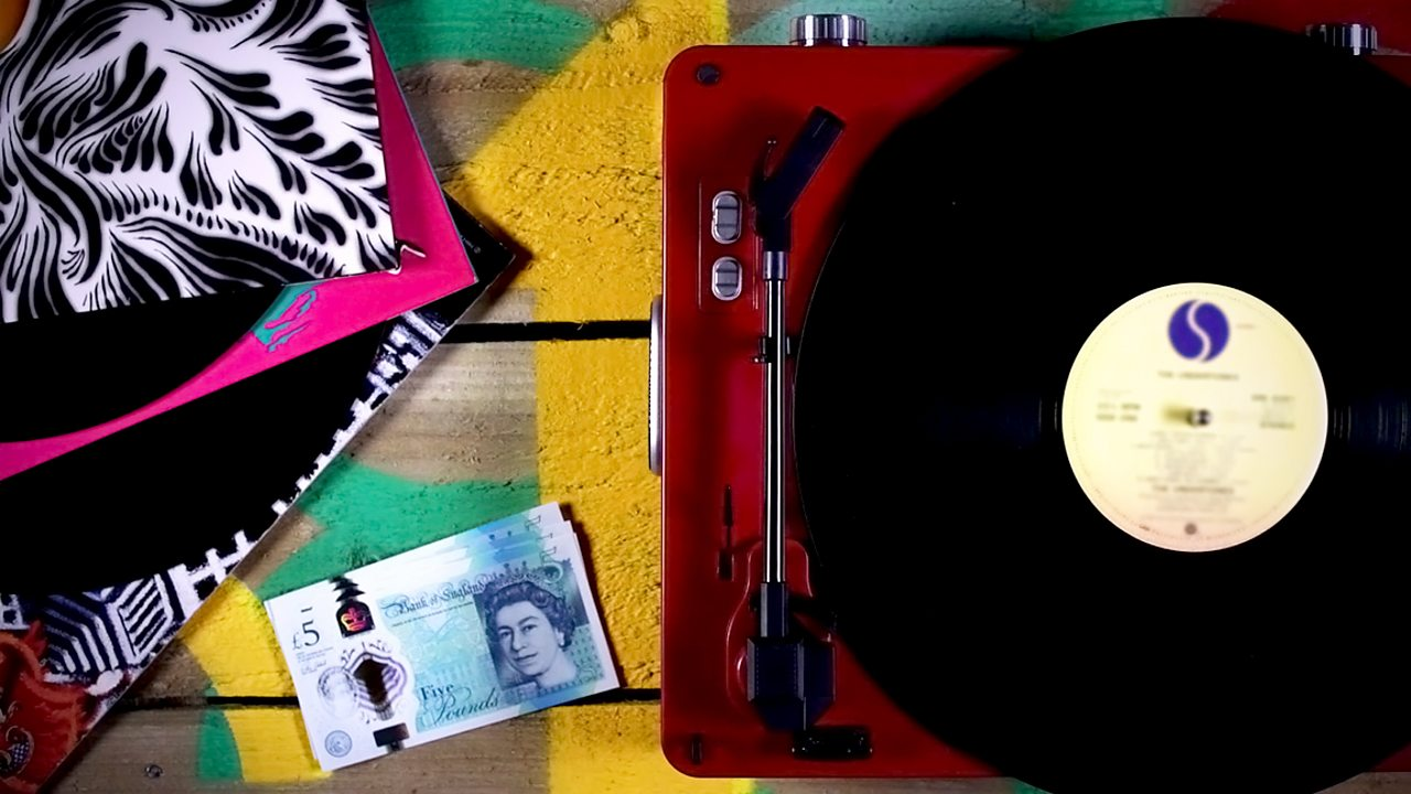 Image of a record player and a pile of vinyls surrounding a stack of £5 notes