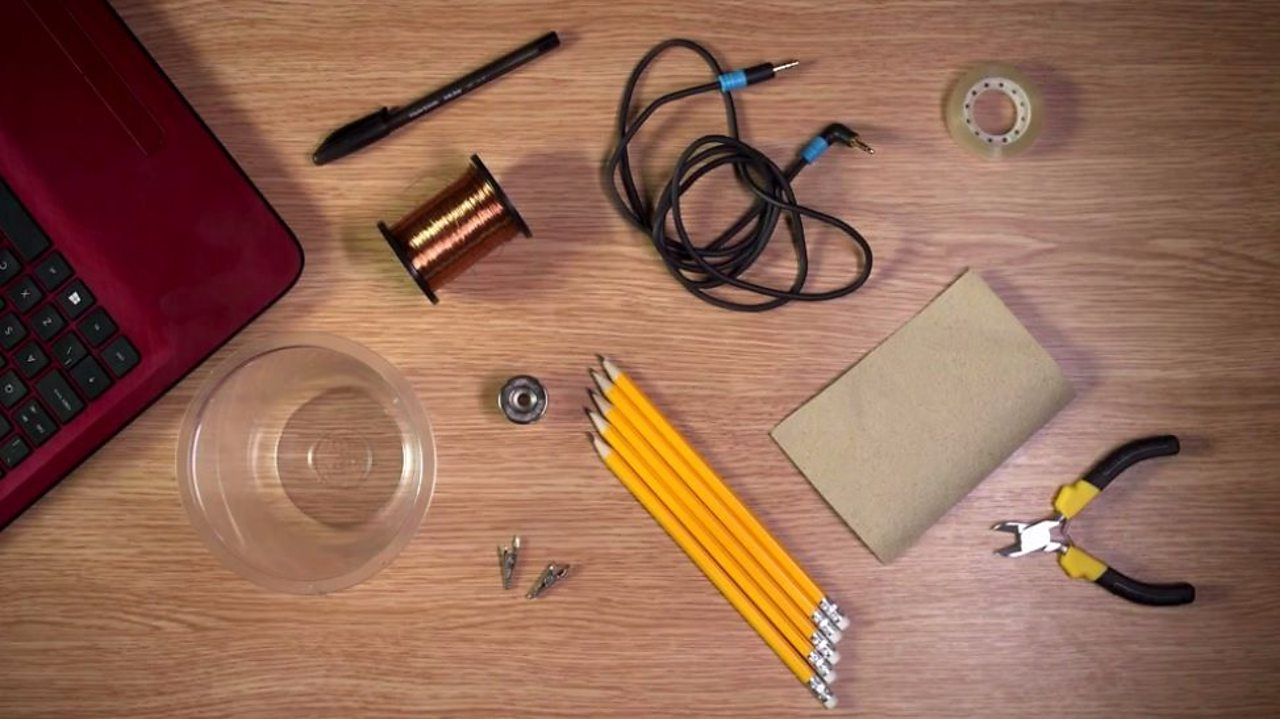 An aerial shot of a pen, pencils, crocodile clips, insulated wire, wire cutters, sandpaper, speaker jack cable and a plastic cup