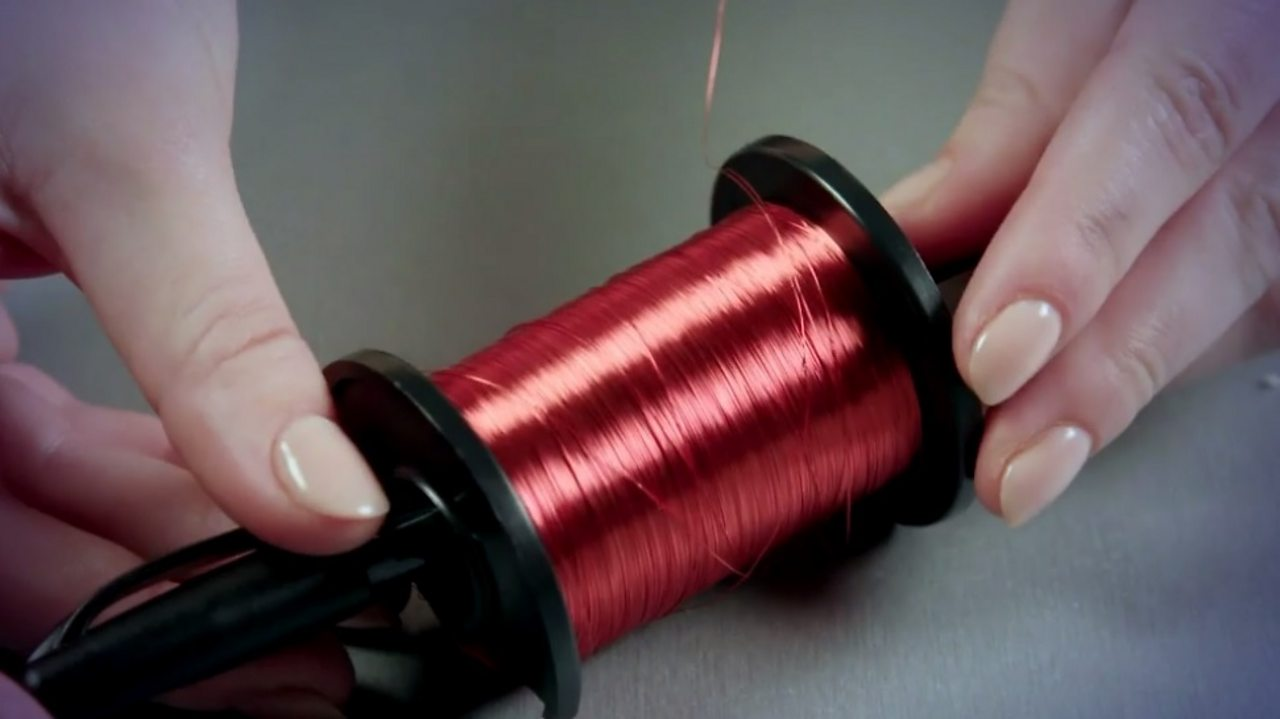 A pen pushed through a spool of copper wire