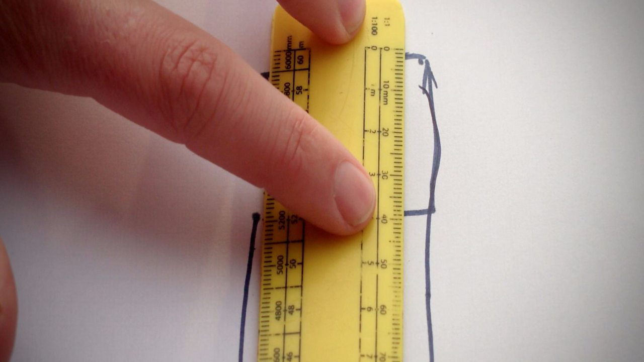 Someone using a ruler to measure the length of the original square that was traced before