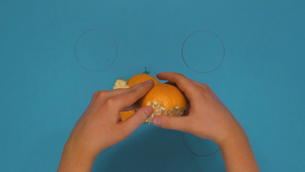 Someone peeling an orange