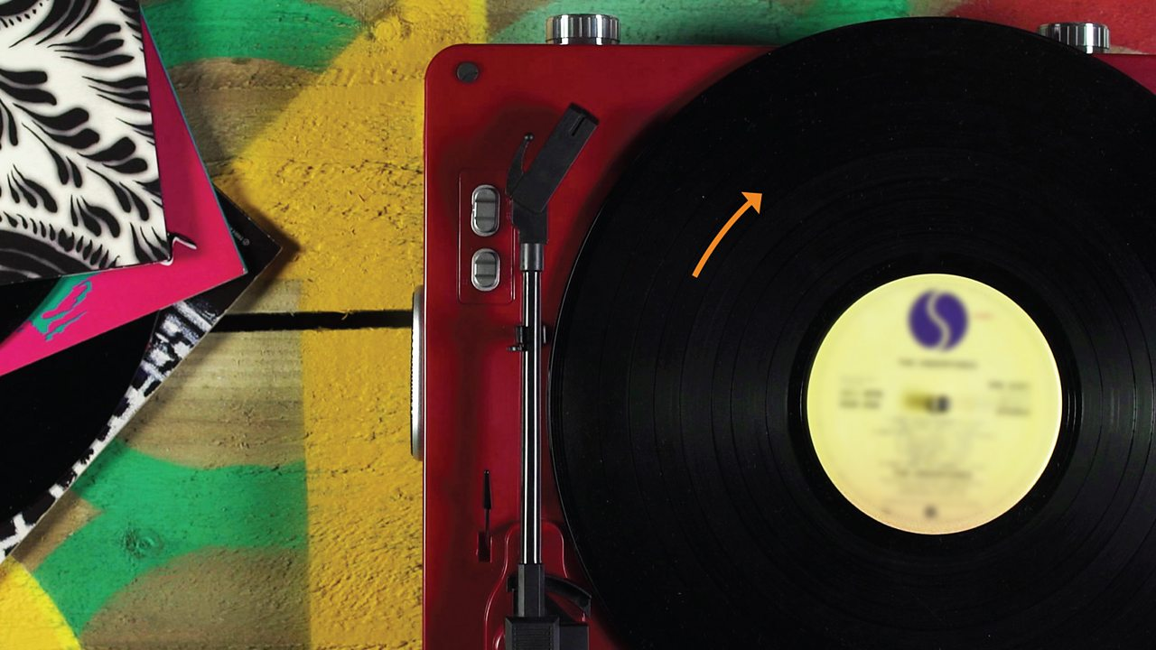 Record on record player with arrow showing rotation
