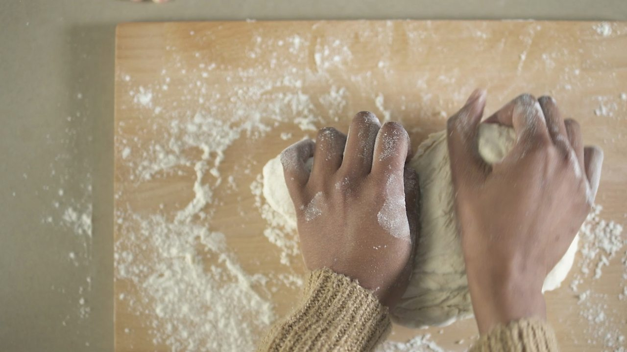 An image of someone kneading the dough