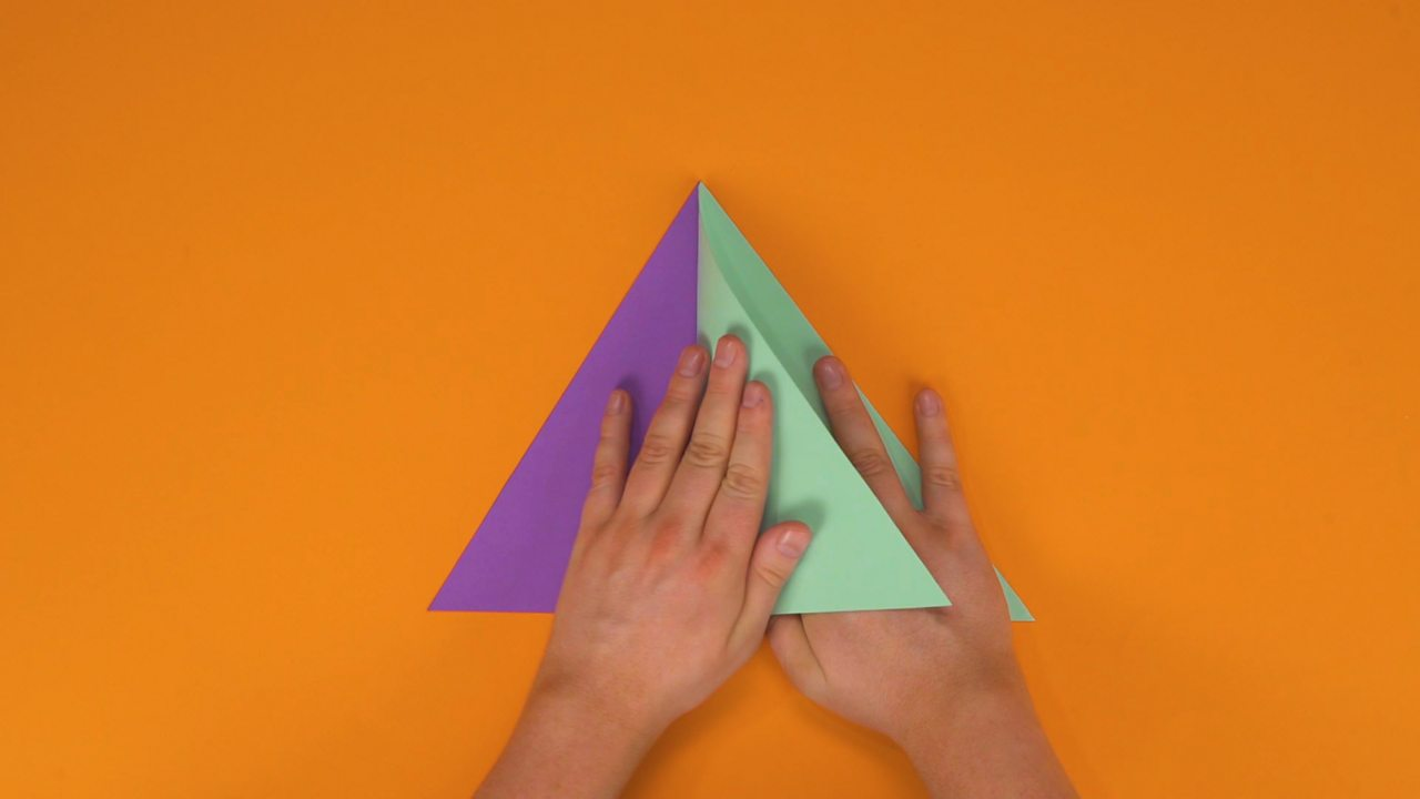 Someone sticking different coloured triangles together