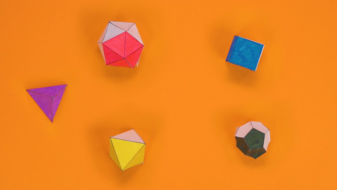 Paper tetrahedron, cube, octahedron, dodecahedron and icosahedron with coloured faces