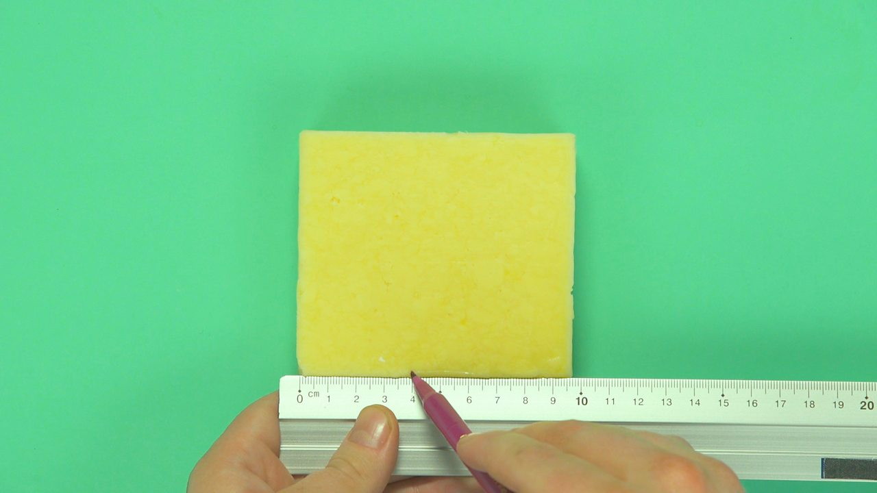 Someone placing a ruler on a block of cheese