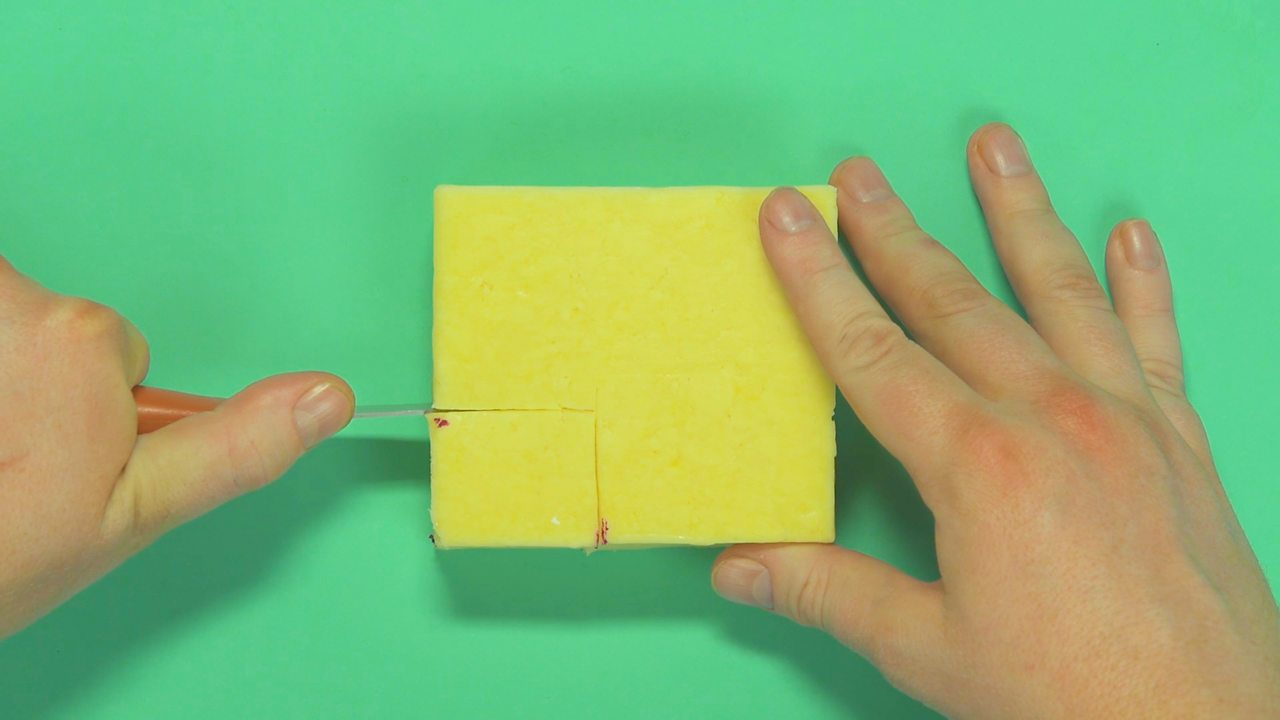 Someone cutting off a block of cheese