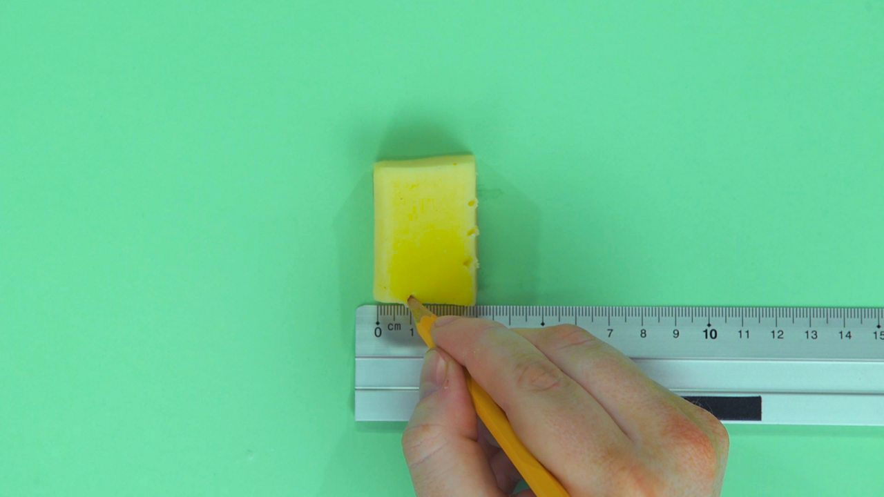 Someone marking their measurements on a block of cheese