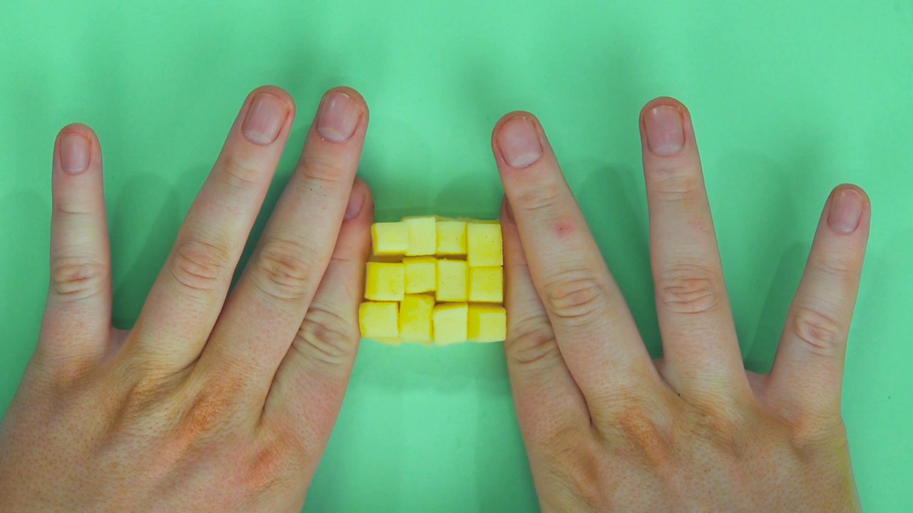 Someone holding together a diced up block of cheese