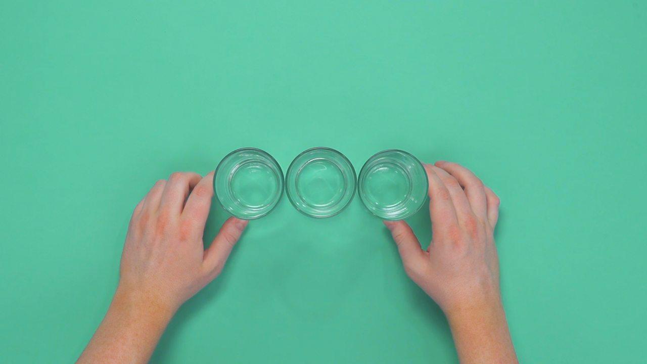 Someone lining up three glasses