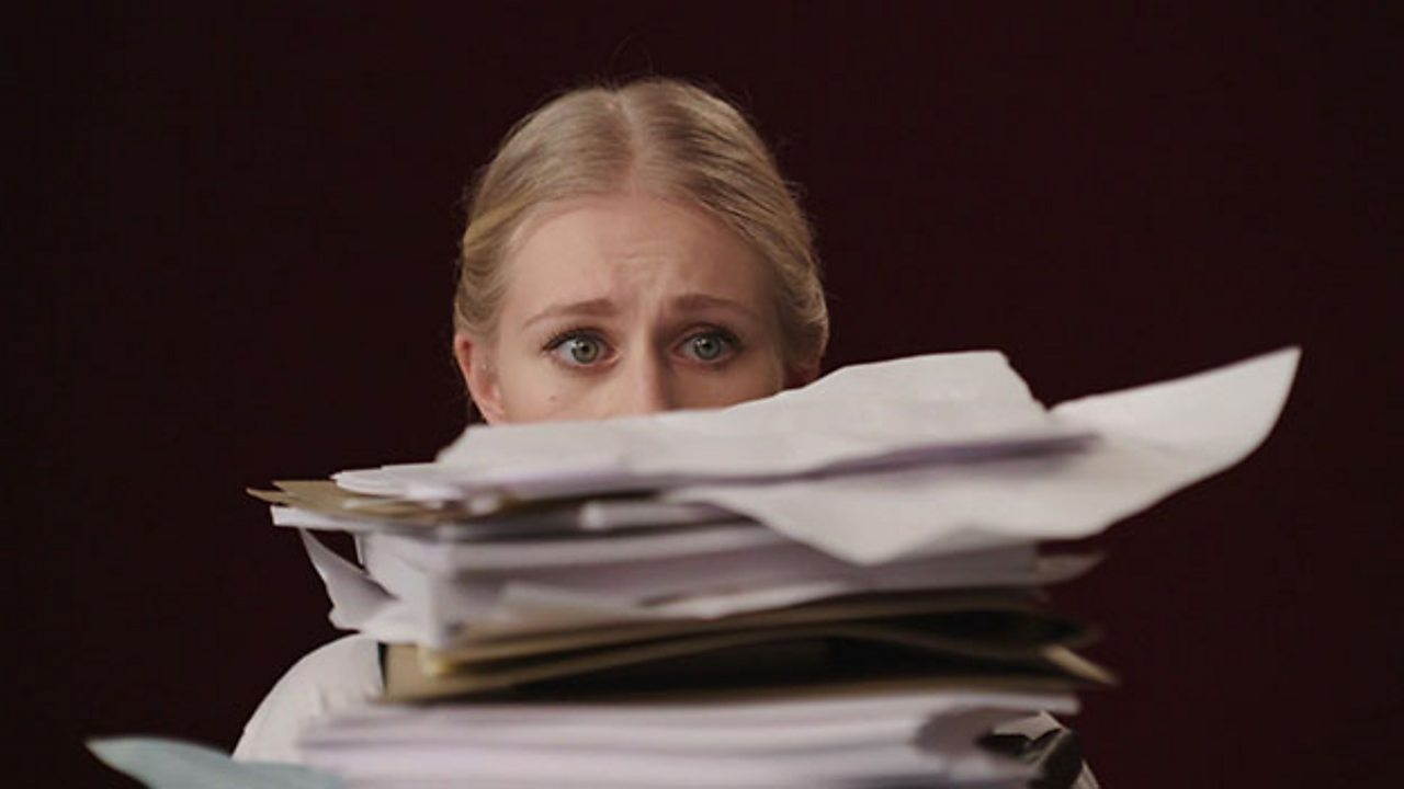 Girl's face is nearly covered by the large pile of work that she is sat behind