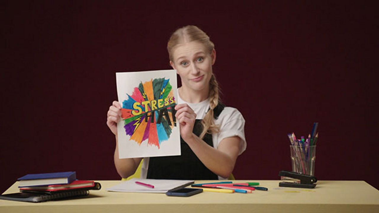 Girl holding up a coloured in image which has the word stress on it