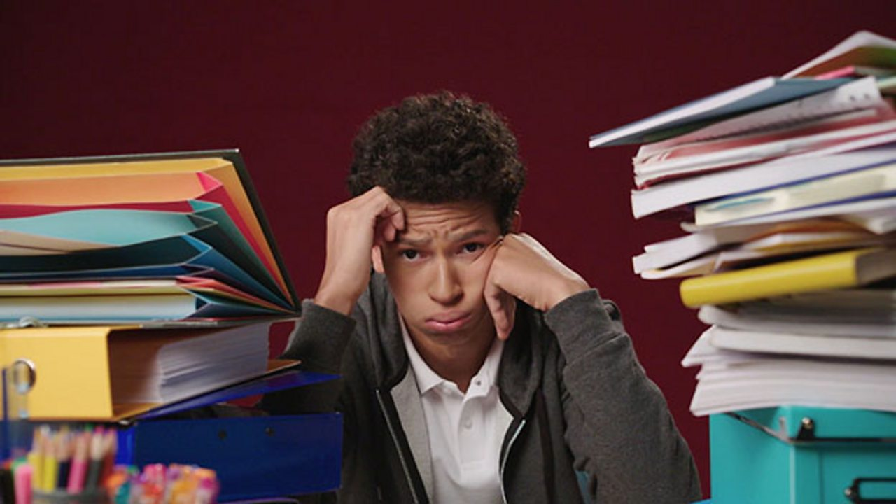 Boy looking sad with two piles of revision notes around him.