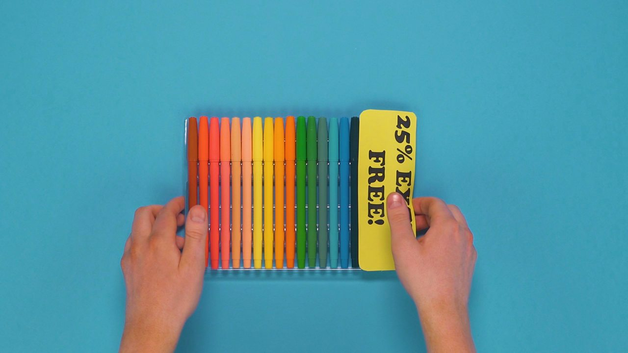 Hands holding pens with 25% extra free label