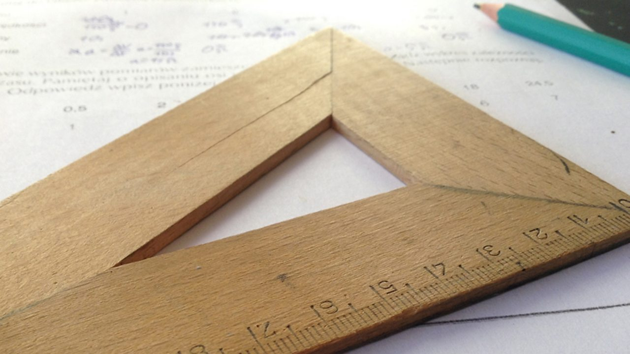 A close up of a wooden set square.