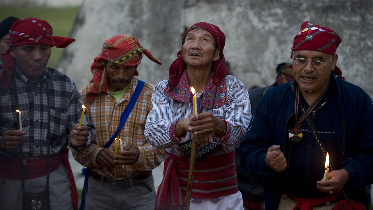 Four Maya men holding candles