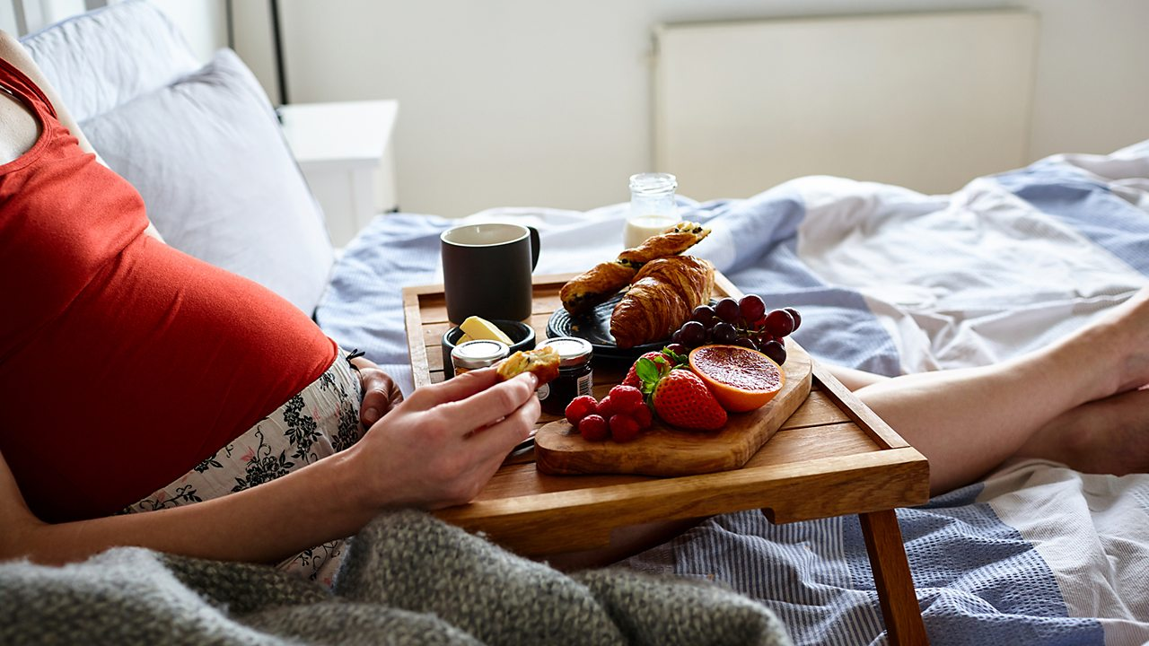 Pregnant woman eating in bed