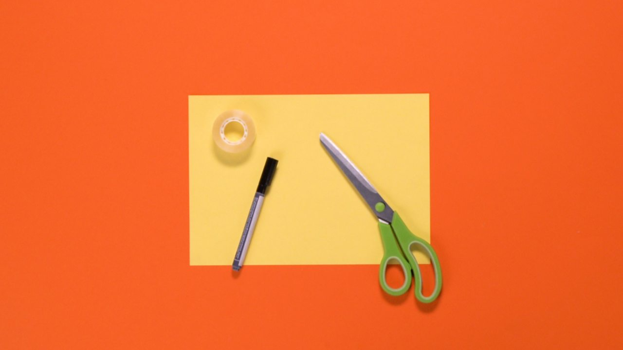 An A4 sheet of paper, scissors, sticky tape and pen are all arranged on a table.