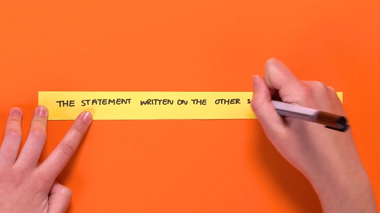 A strip of paper being written on.