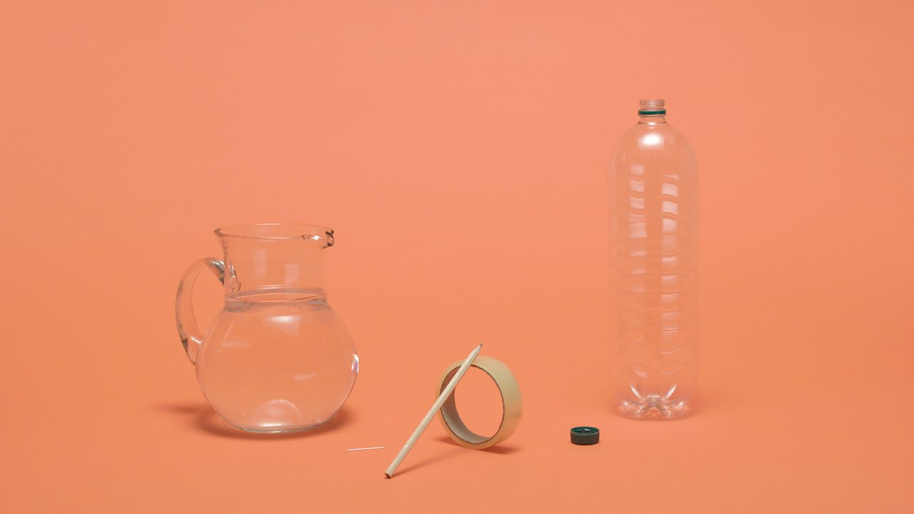 WHAT YOU NEED - An empty plastic bottle, some sticky tape, a pin, a pencil and a jug of water.