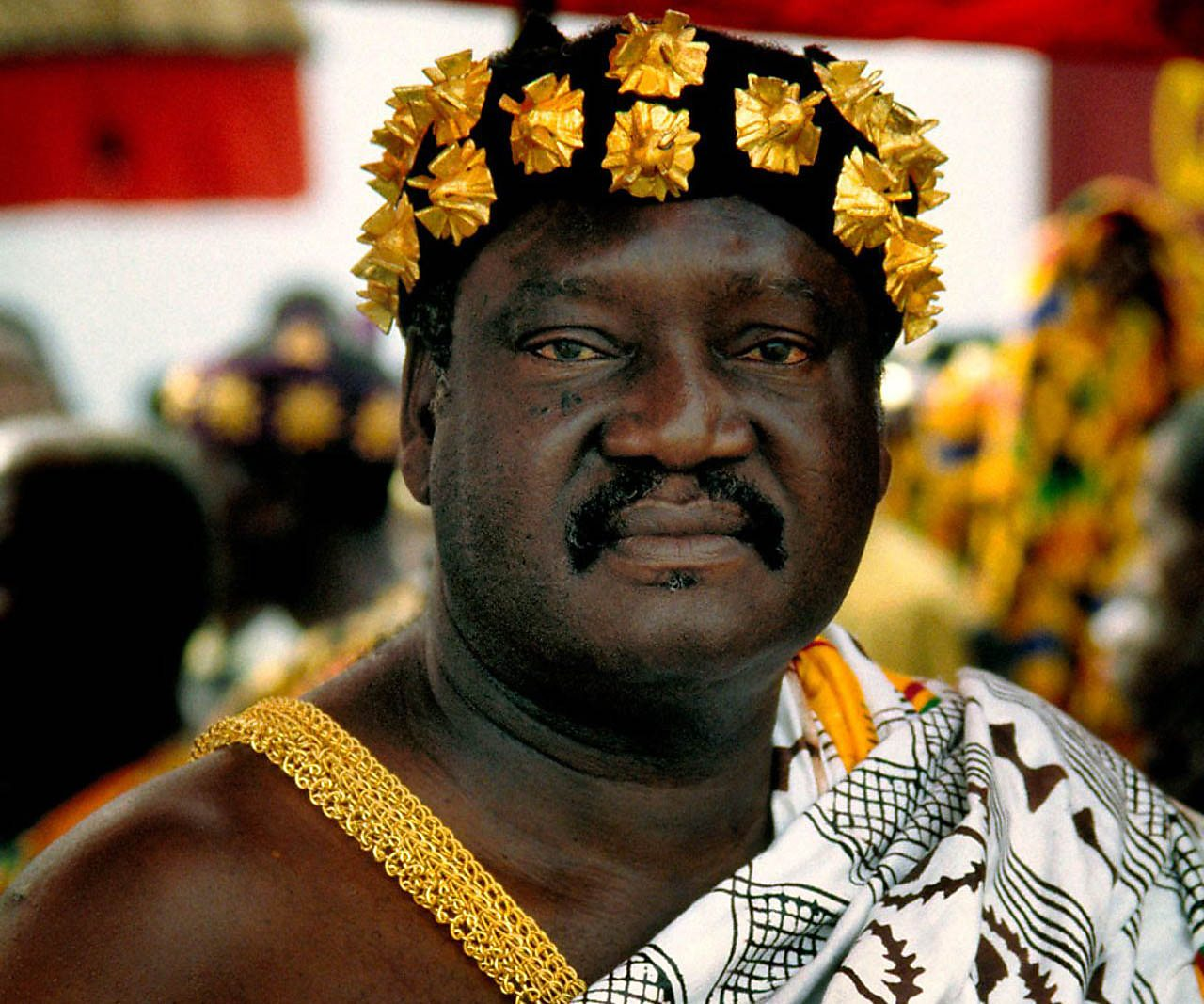 An Asante chief dressed in robes and crown.