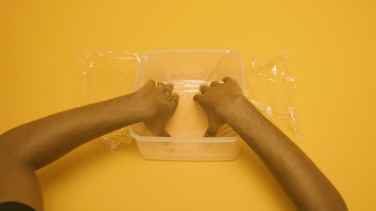 A person lining a box with cling film