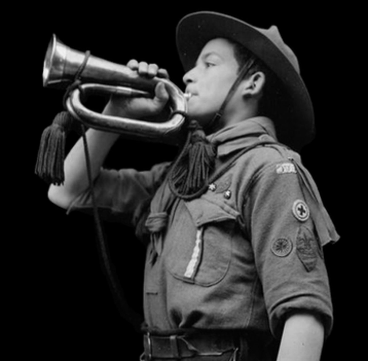 A boy scout sounding the alarm during World War One.