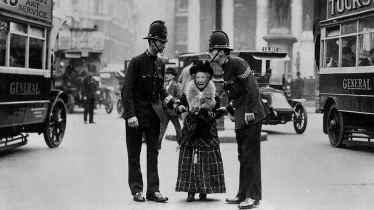 London traffic police helping an elderly lady across a busy street in the early 1900s
