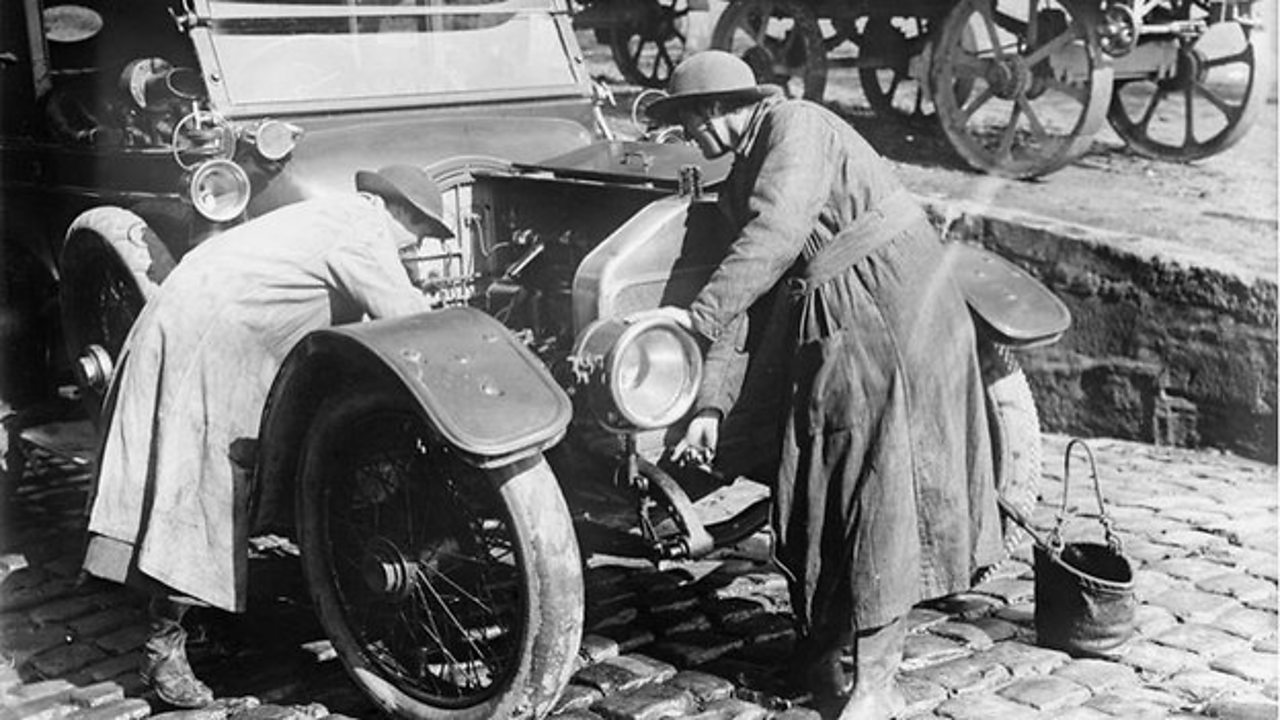 Women's Army Auxiliary Corps mechanics at work on a car engine in France
