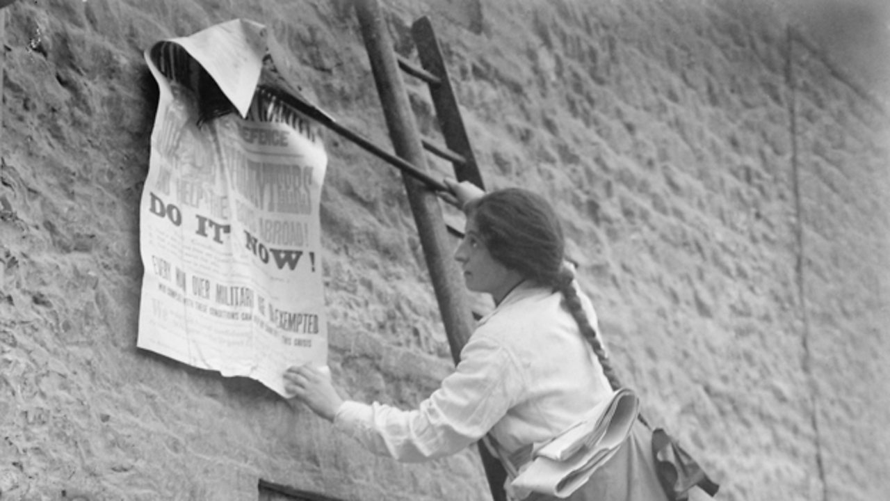 Photograph of a girl posting a World War One recruitment poster on the side of a building