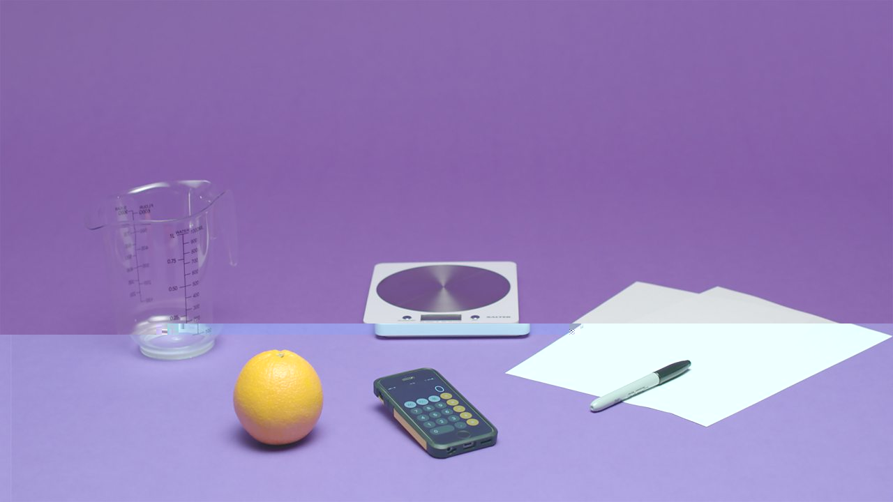 Orange, measuring jug, scales, pen, paper and calculator