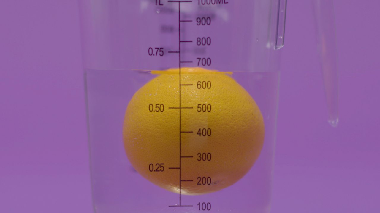 Orange floating in water inside a measuring jug