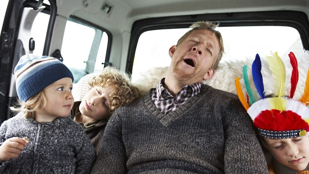 A man snoring in the back of his car with his children