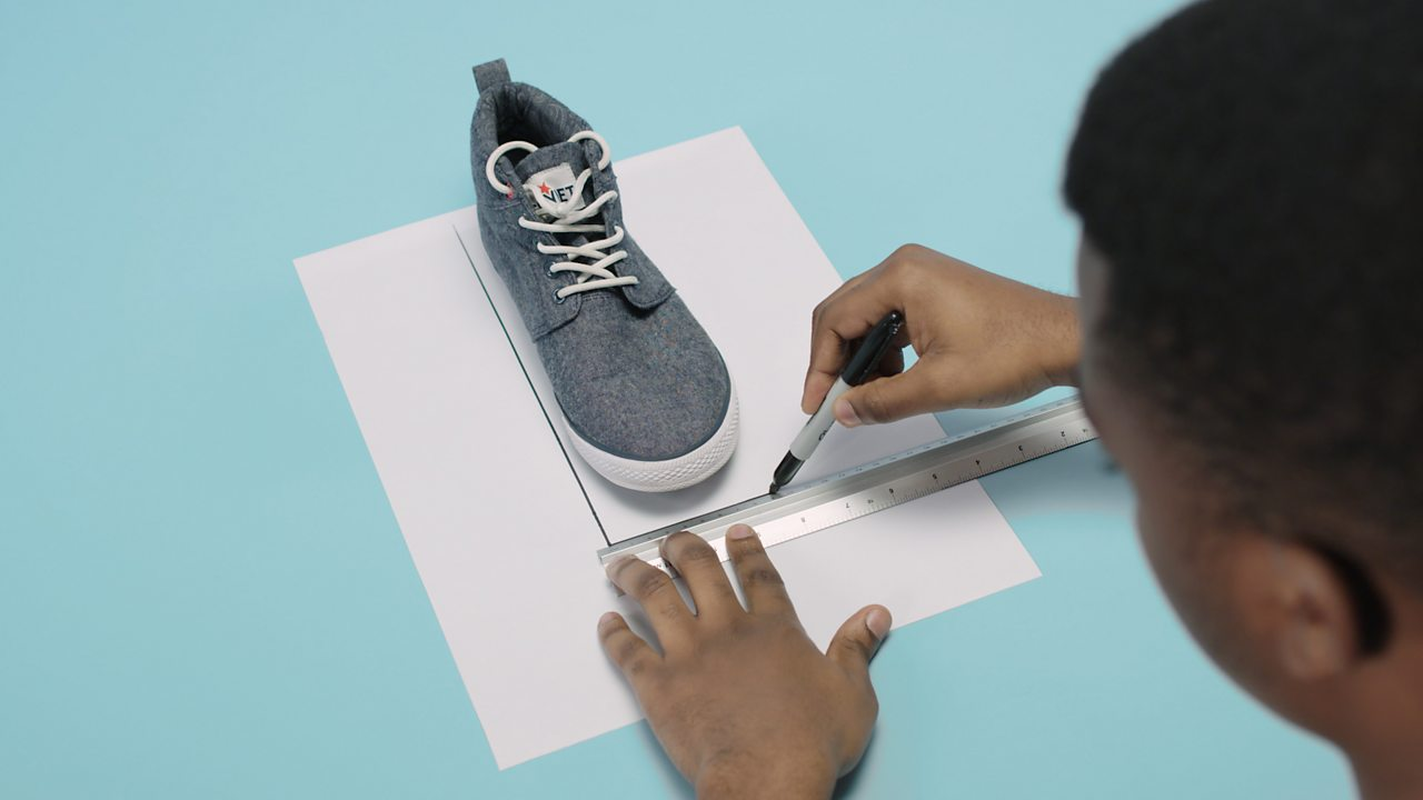 Stand on a sheet of paper and use a pen and a ruler to draw a rectangle around the trainer.
