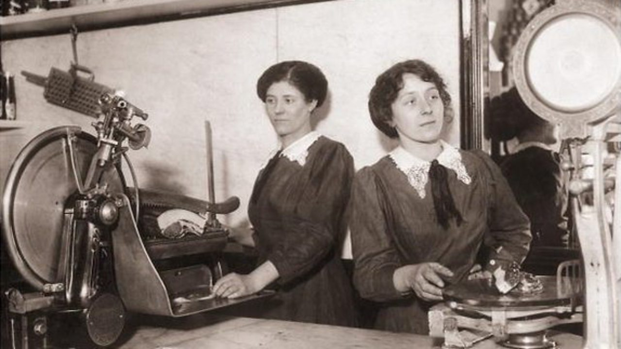 Female shop assistants slice meat and weigh it for a customer in the early 1900s