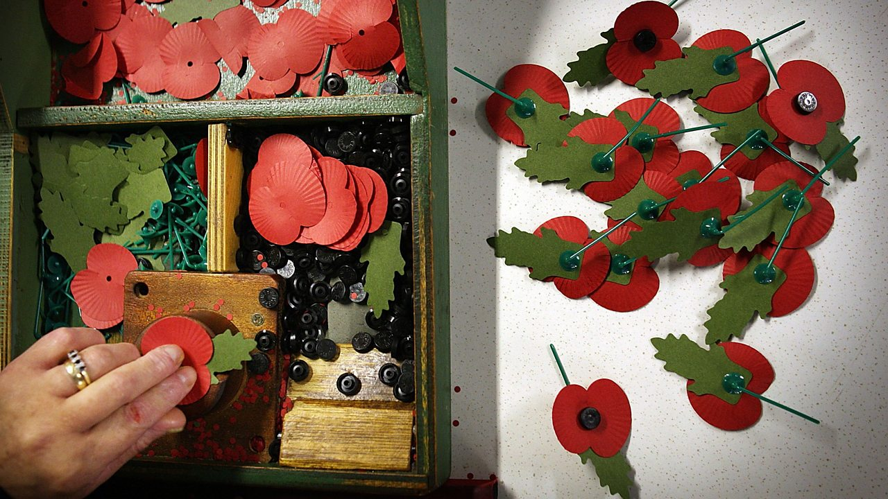 A box of paper poppies being constructed by a hand