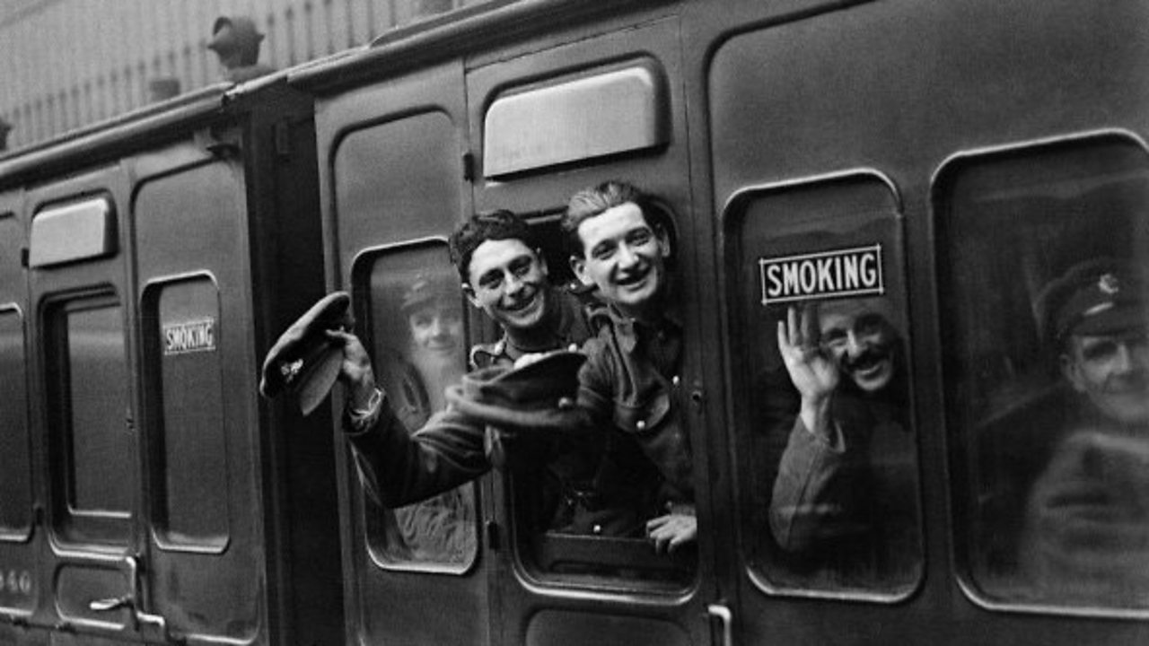 World War One soldiers waving through a train carriage window