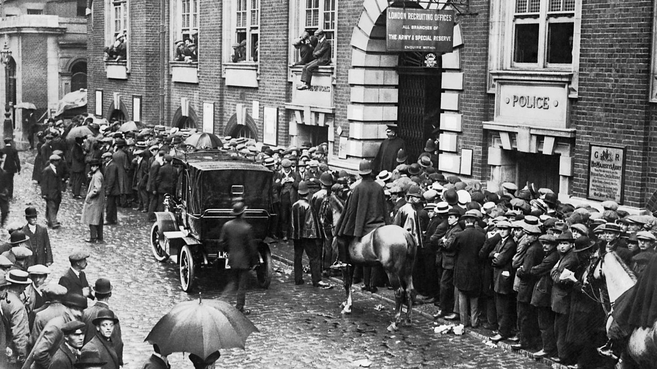 Young men queuing eagerly along a street outside a recruitment station in World War One