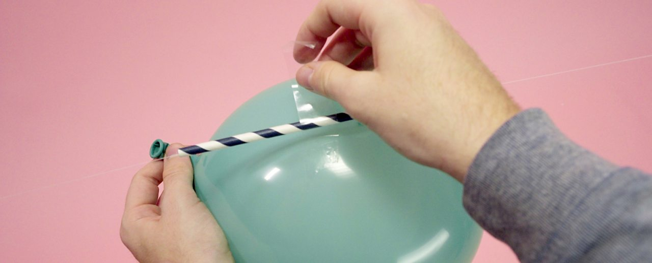 Tape the straw to the balloon.