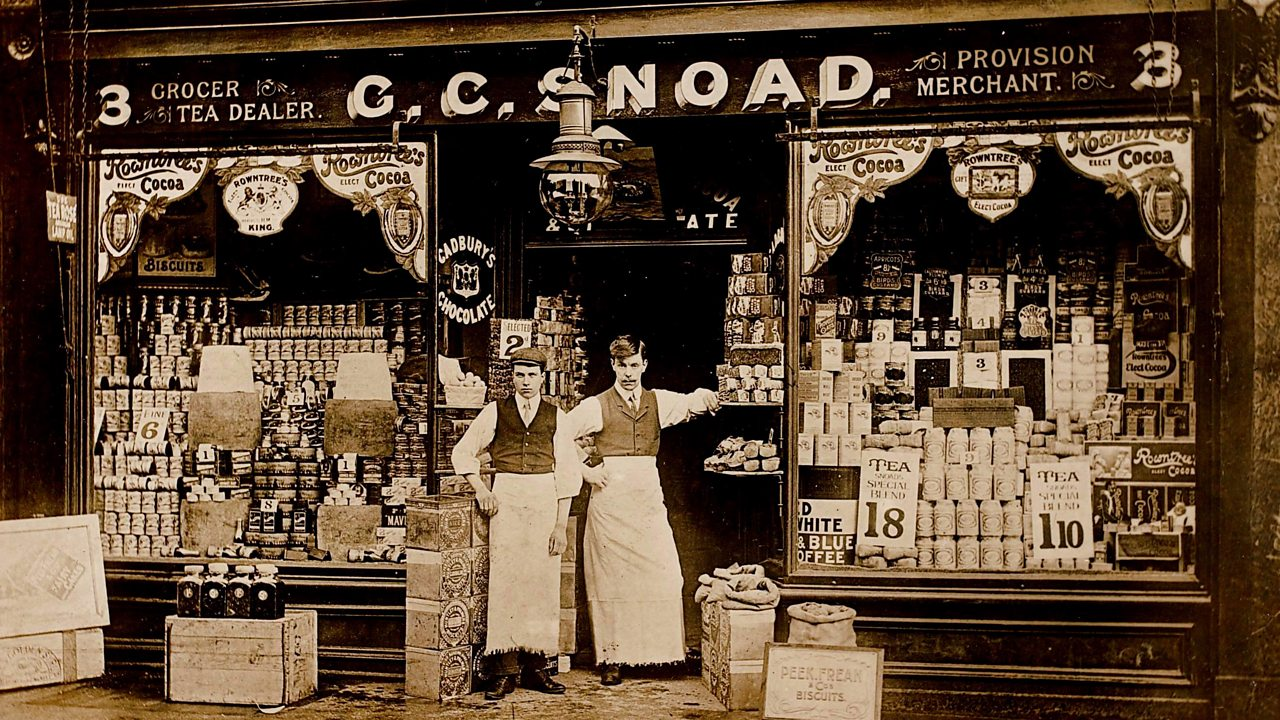 A photograph of two grocers outside their shop front in World War One